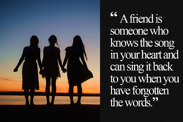 Three friends standing together with friendship saying card